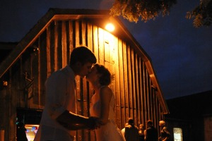 kissing at barn wedding